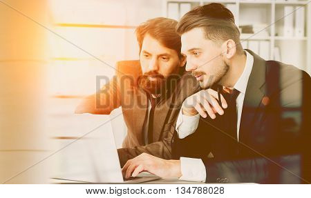 Two businesspeople sitting at office desk discussing project on laptop. Toned image