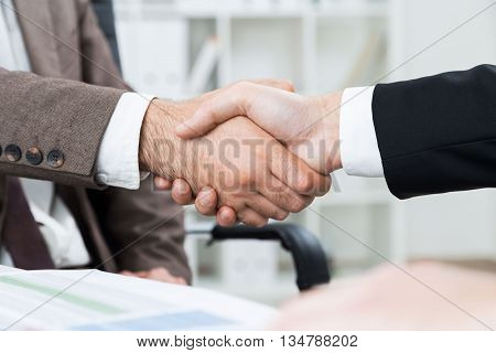 Businessmen shaking hands on blurry office background. Closeup
