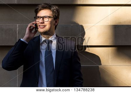 Handsome young businessman with glasses having mobile phone conversation outside on concrete tile background
