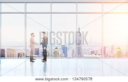 Businesspeople shaking hands in interior with New York city in the background. Double exposure