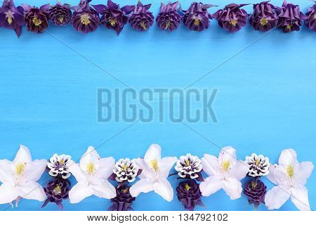 Frame with flowers on blue wooden background.