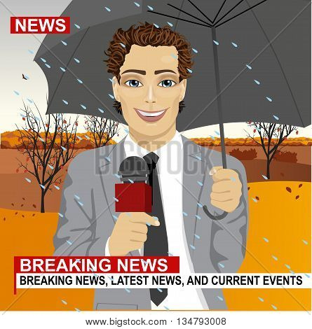 Successful handsome male journalist in light grey suit working in rainy weather outdoors in the park holding microphone and umbrella in live broadcasting