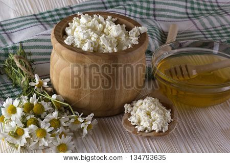 Honey, cottage cheese, and chamomile flowers on wooden background