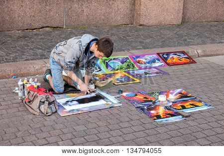 SAINT PETERSBURG RUSSIA - AUGUST 7 2015: The young artist paints a pictures on a city street