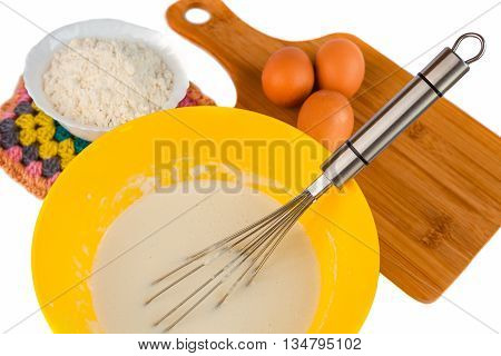 Baking ingredients for making pancake batter batter flour eggs bowls cutting board for cooking and metal whisk or egg beater for whipping on white background