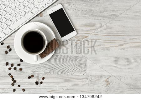 Keyboard, cup of hot coffee and smartphone on wooden surface with copy space. Workplace of office man. Office stuff. Willingness to work overtime. Conductive working environment