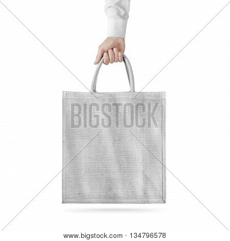 Blank white cotton eco bag design mockup isolated, holding hand, clipping path. Textile cloth bag mock up template hold arm. Tote shoe consumer reusable organic craft package. Carrier recycle bag