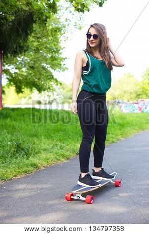 young woman in the park with a longboard