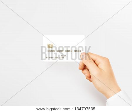 Hand holding blank white credit card mockup isolated. Empty plastic card mock up hold in arm. Clear surface bank card with gold emboss numbers. Debit card concept design presentation golden money card