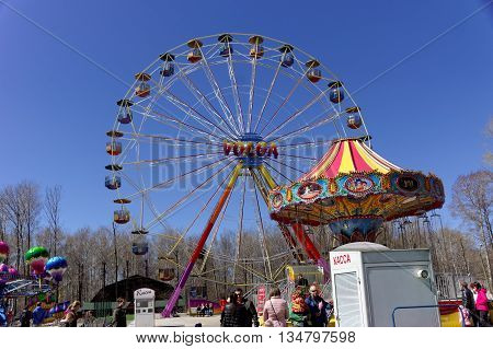 Nizhny Novgorod, Russia - May 2.2013. Ferris wheel in the park Switzerland. On a warm spring day, the townspeople with children having fun ride on the carousel