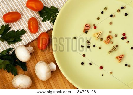 Word Pasta from macaroni Letters witch fresh tomatoes, herbs and mushrooms