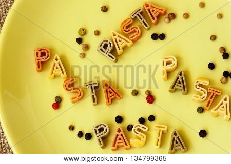 Word pasta made from macaroni Letters on the plate. Close-up. Backgraund