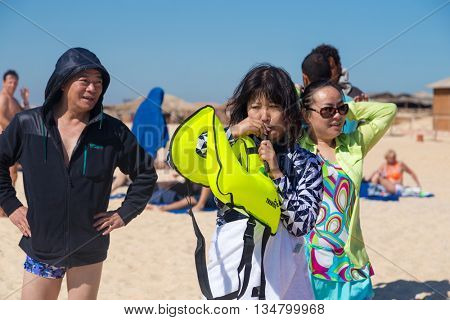 PARADISE ISLAND, EGYPT - FEBRUARY 12, 2016: Chinese tourist blowing up the life jacket at the beach.