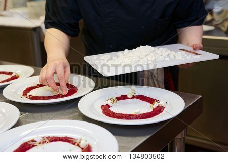 Chef is cooking set of appetizers, putting soft cheese