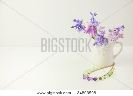 Styled stock floral image bluebells in a pretty white china jug with a necklace beside the jug. Copy space for your business promotion instagram message or headline.