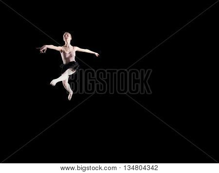 Young beautiful ballerina on a black background in studio