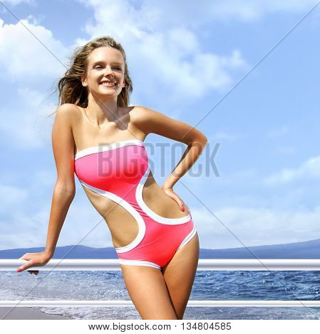 happy woman sunbathing in pink bathing suit on beach