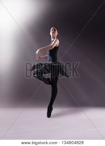 Young ballerina in black outfit posing on toes, studio background.