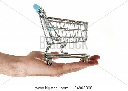 man hand holding in palm little metal shopping trolley in commerce and business concept isolated on white background