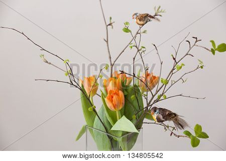 Fresh spring bunch of orange tulips and green leaves and two small birds in nice cristal glass vase.