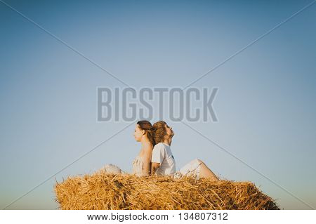 Image of young man and woman sitting on haystack