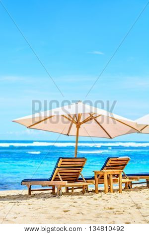 A lounge chair at the beach under the shade of an umbrella on a beautiful beach in Bali