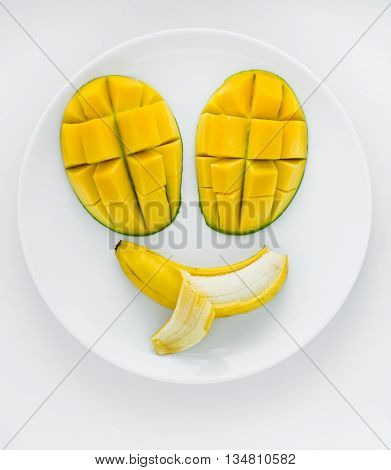 A face made from mangoes for eyes and a banana for mouth with a tongue poking out.