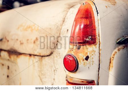Rear view of old abandoned car with cracked tail light covered with web. Color-toning effect applied.