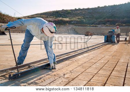 Worker in a tufa quarry while setting the platform for a circular sawing machine