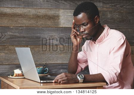Busy-looking African Entrepreneur Working On New Business Strategy, Sitting In Front Of His Laptop,