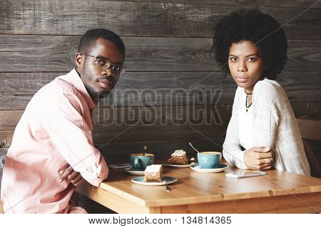 Handsome African American Student In Shirt And Glasses Sitting At A Cafe With His Dark-skinned Femal
