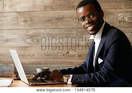 Young Attractive Smiling African Male, Typing A Message Via Social Networks On Laptop, Sitting At A