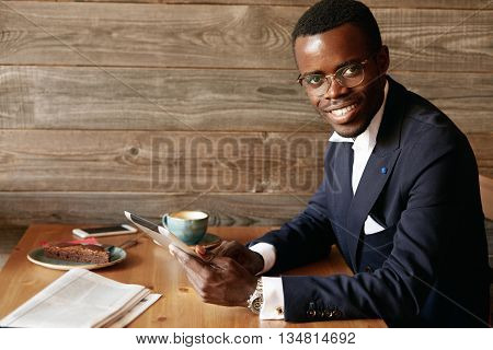 Happy Successful Young African Businessman In Spectacles And Formal Wear, Sitting At The Table With