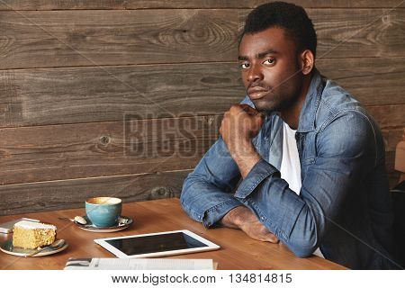 Serious African American Man In Denim Shirt Sitting In A Café. He Has Coffee, Dessert, Digital
