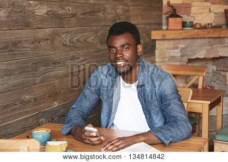 Beautiful Portrait Of African Man Sitting In Café With Free Wireless Connection, Drinking Fresh