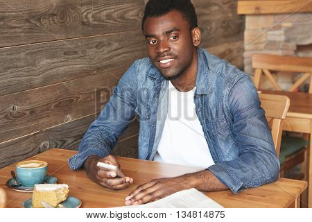 Young African Gentleman In Casual Clothes Holding Smartphone And Sitting In Comfy Café. Happy M