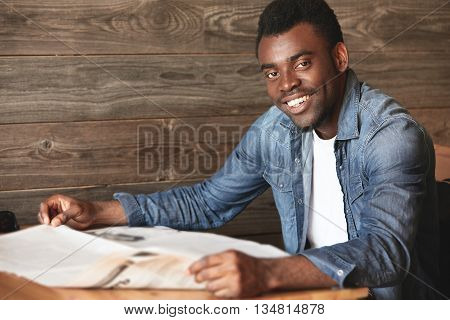 Young African American Man Sitting In Cosy Café, Reading Morning Newspaper. Dark-skinned Youngs