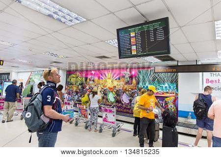 PHUKET THAILAND - 29 MAY 2016: Tourists check air flight form display at Phuket international airport departures area at Phuket international airport.