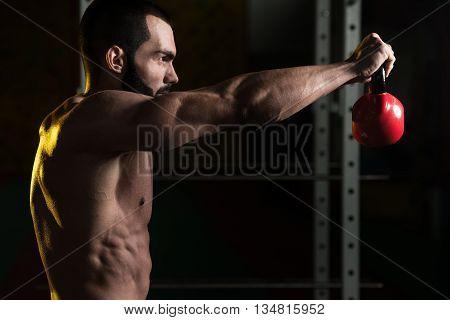 Fitness Man Using Kettlebells Inside Gym