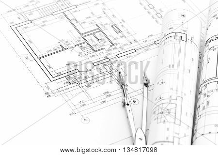 Rolls Of Architectural Blueprints And House Plan With Drawing Compass