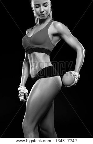 Beautiful sportly fitness woman holding an orange next to their buttocks. Girl's hip and an orange. Anti-cellulite program