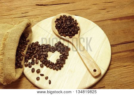 Coffee beans whit wooden spoon on wood; Heart shaped coffee beans
