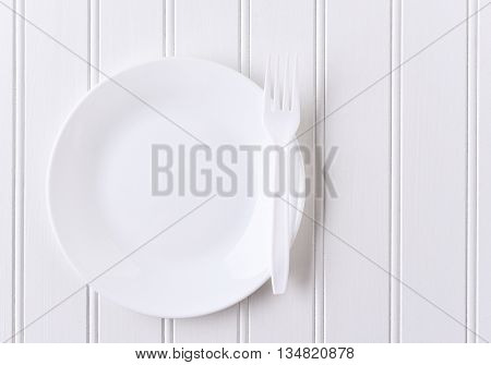 Top view of a white plate and white plastic fork on a white beadboard surface. Horizontal format with copy space.