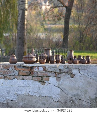 pottery clay pots standing on an old brick in the park in the afternoon