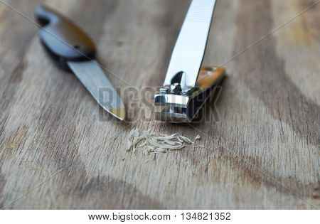 clipper and nail file on wooden board