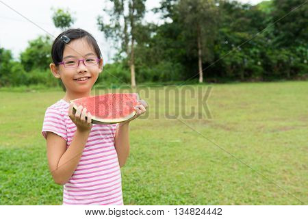 Asian child with big slice of watermelon in the park