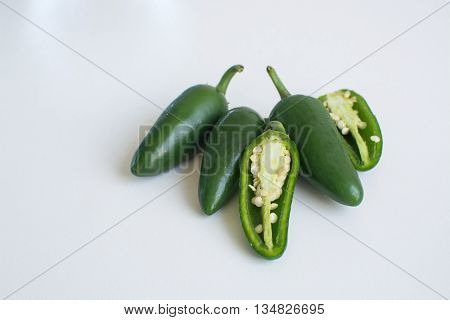 Bright green jalapeno hot peppers on white background