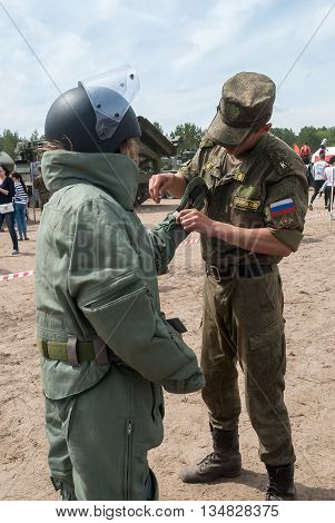 Tyumen Russia - June 11 2016: Race of Heroes project on the ground of the highest military and engineering school. Exhibition of weapon. Girl - visitor of show puts on sapper suit