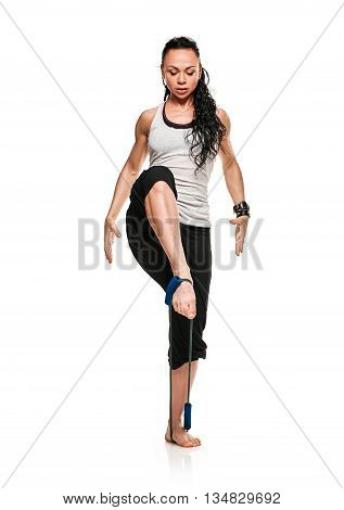 brunette athletic woman exercising with rubber tape by legs on white background