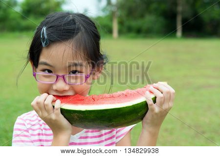 Asian child eating watermelon in the park